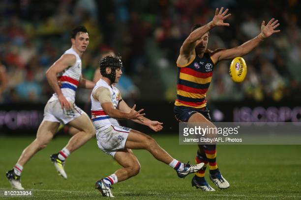 Caleb Daniel of the Bulldogs competes with Taylor Walker of the Crows during the 2017 AFL round 16 match between the Adelaide Crows and the Western...