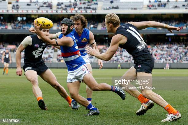 Caleb Daniel of the Bulldogs handballs during the round 17 AFL match between the Carlton Blues and the Western Bulldogs at Melbourne Cricket Ground...