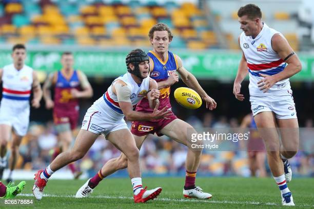 Caleb Daniel of the Bulldogs handballs during the round 20 AFL match between the Brisbane Lions and the Western Bulldogs at The Gabba on August 5...