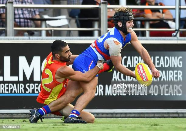 Caleb Daniel of the Bulldogs handballs whilst being tackled by Adam Saad of the Suns during the round 18 AFL match between the Western Bulldogs and...
