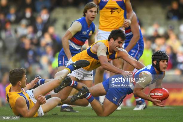Caleb Daniel of the Bulldogs handballs whilst being tackled by Andrew Gaff of the Eagles during the round 15 AFL match between the Western Bulldogs...