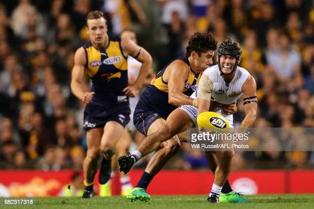 Caleb Daniel of the Bulldogs handpasses the ball under pressure from Sharrod Wellingham of the Eagles during the round eight AFL match between the...