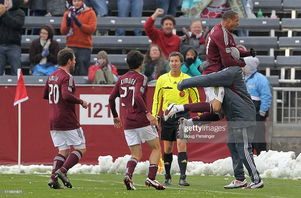 Caleb Folan of the Colorado Rapids leaps into the arms of a teammate as he celebrates his goal in the first half against DC United along with...