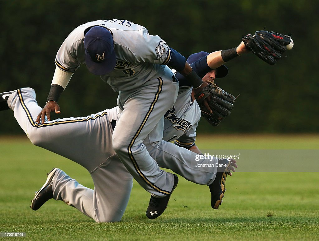Caleb Gindl #15 of the Milwaukee Brewers appears to make a catch while colliding with teammate <a gi-track='captionPersonalityLinkClicked' href=/galleries/search?phrase=Jean+Segura&family=editorial&specificpeople=7521808 ng-click='$event.stopPropagation()'>Jean Segura</a> #9 on a ball hit by Anthnoy Rizzo of the Chicago Cubs in the 1st inning at Wrigley Field on July 29, 2013 in Chicago, Illinois.