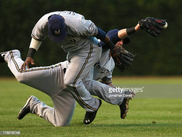 Caleb Gindl of the Milwaukee Brewers appears to make a catch while colliding with teammate Jean Segura on a ball hit by Anthnoy Rizzo of the Chicago...