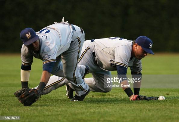 Caleb Gindl of the Milwaukee Brewers drops the ball after colliding with teammate Jean Segura on a ball hit by Anthnoy Rizzo of the Chicago Cubs in...