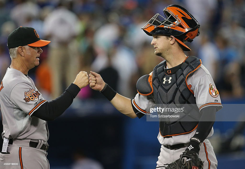Caleb Joseph #36 of the Baltimore Orioles celebrates their victory hitting coach Jim Presley #15 during MLB game action against the Toronto Blue Jays on August 7, 2014 at Rogers Centre in Toronto, Ontario, Canada.