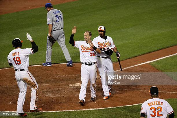 Caleb Joseph of the Baltimore Orioles celebrates with Chris Davis and Adam Jones after scoring the winning run on a passed ball thrown by Joe Biagini...