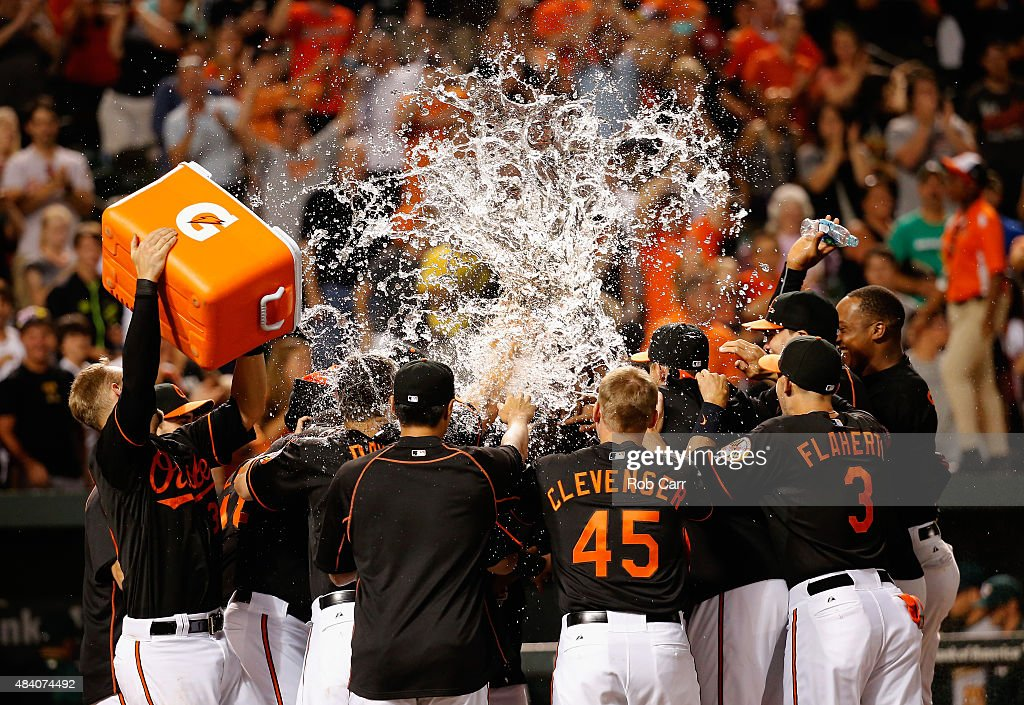 Caleb Joseph #36 of the Baltimore Orioles (L) dumps water on <a gi-track='captionPersonalityLinkClicked' href=/galleries/search?phrase=Manny+Machado&family=editorial&specificpeople=5591039 ng-click='$event.stopPropagation()'>Manny Machado</a> #13 (C) after Machado hit a walk off two RBI home run to give the Orioles an 8-6 win the thirteenth inning at Oriole Park at Camden Yards on August 14, 2015 in Baltimore, Maryland.