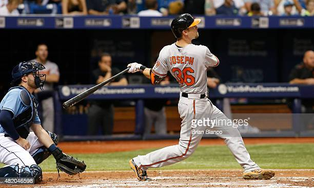 Caleb Joseph of the Baltimore Orioles hits a tworun home run in front of catcher Curt Casali of the Tampa Bay Rays during the fourth inning of a game...