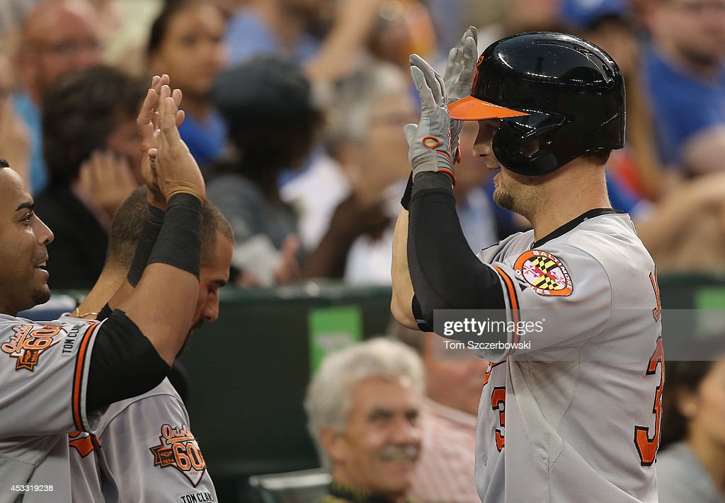 Caleb Joseph #36 of the Baltimore Orioles is congratulated by Neslon Cruz #23 after hitting a two-run home run in the fourth inning during MLB game action against the Toronto Blue Jays on August 7, 2014 at Rogers Centre in Toronto, Ontario, Canada.