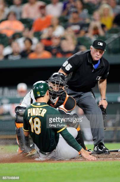 Caleb Joseph of the Baltimore Orioles tags out Chad Pinder of the Oakland Athletics in the eighth inning at Oriole Park at Camden Yards on August 22...