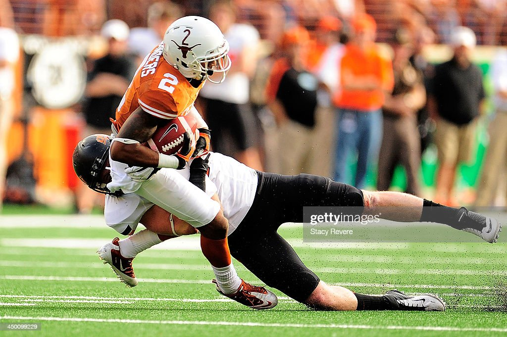 Caleb Lavey #45 of the Oklahoma State Cowboys brings down Kendall Sanders #2 of the Texas Longhorns during a game at Darrell K Royal-Texas Memorial Stadium on November 16, 2013 in Austin, Texas. Oklahoma State won the game 38-13.