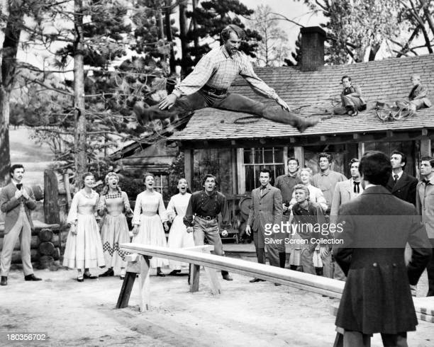 Caleb Pontipee played by American jazz and ballet dancer Matt Mattox leaps above a sawhorse in 'Seven Brides For Seven Brothers' directed by Stanley...
