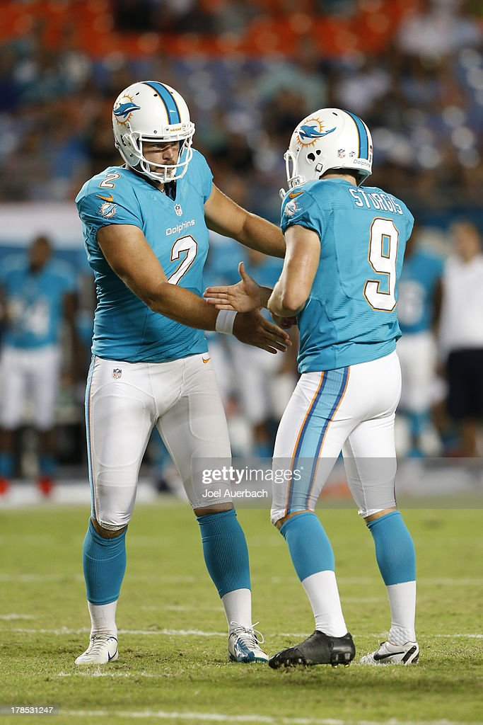 Caleb Sturgis #9 is congratulated by Brandon Fields #2 of the Miami Dolphins after he kicked a field goal against the New Orleans Saints with three minutes left during a preseason game on August 29, 2013 at Sun Life Stadium in Miami Gardens, Florida. The Dolphins defeated the Saints 24-21.