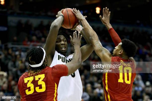 Caleb Swanigan of the Purdue Boilermakers handles the ball while being guarded by Solomon Young and Darrell Bowie of the Iowa State Cyclones in the...