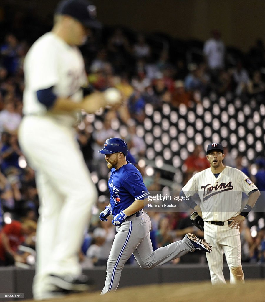 Caleb Thielbar #56 and <a gi-track='captionPersonalityLinkClicked' href=/galleries/search?phrase=Trevor+Plouffe&family=editorial&specificpeople=5722348 ng-click='$event.stopPropagation()'>Trevor Plouffe</a> #24 of the Minnesota Twins look on as <a gi-track='captionPersonalityLinkClicked' href=/galleries/search?phrase=Adam+Lind&family=editorial&specificpeople=3911783 ng-click='$event.stopPropagation()'>Adam Lind</a> #26 of the Toronto Blue Jays rounds the bases after hitting a three-run home run during the ninth inning of the game on September 7, 2013 at Target Field in Minneapolis, Minnesota. The Blue Jays defeated the Twins 11-2.