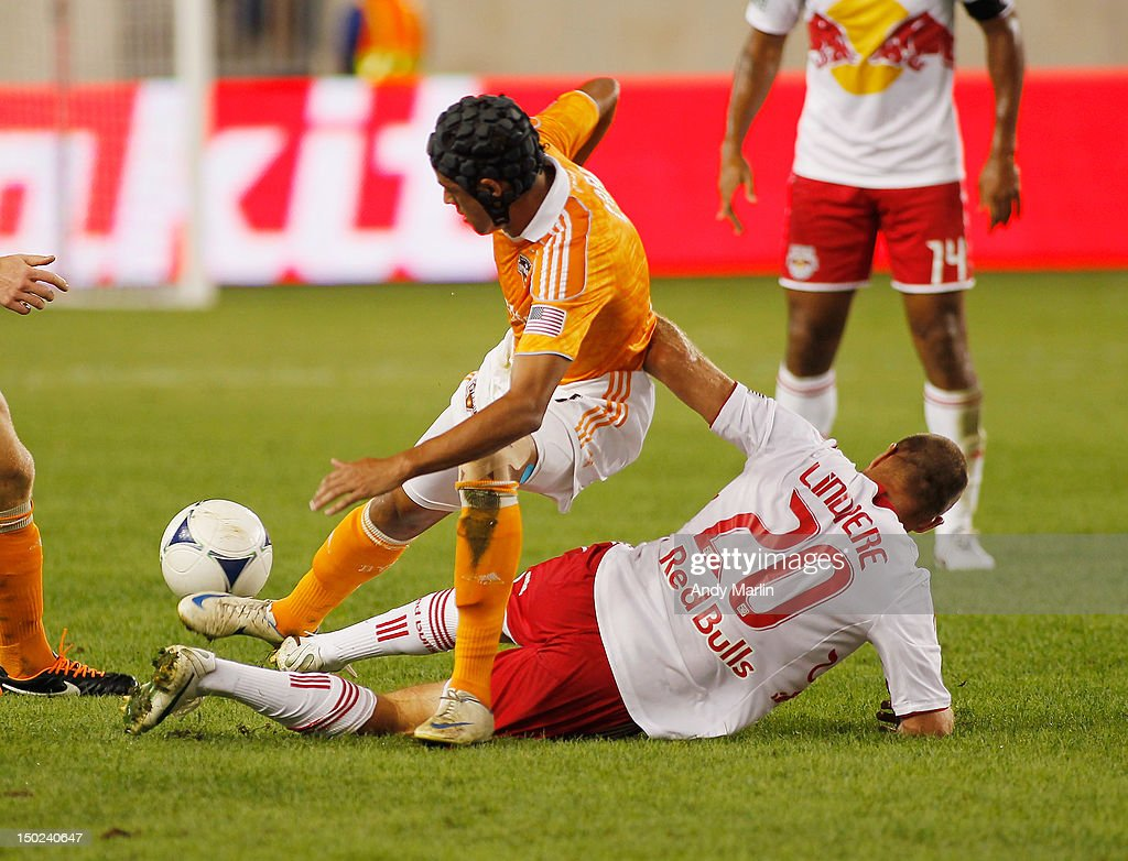 Calen Carr of the Houston Dynamo and Joel Lindpere of the New York Red Bulls battle for a loose ball during the game at Red Bull Arena on August 10...