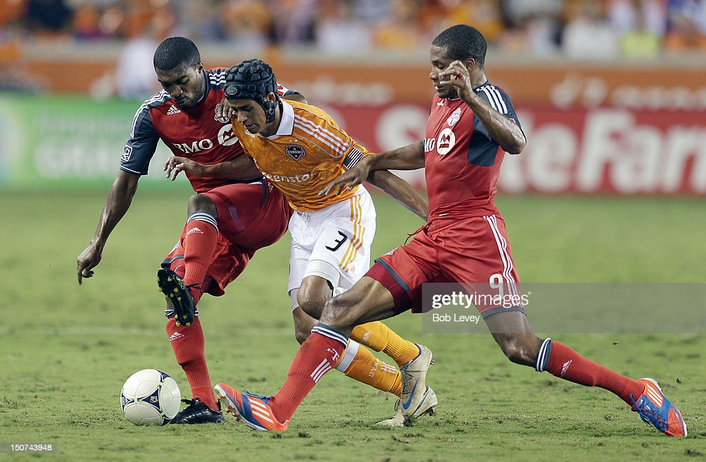 Calen Carr of the Houston Dynamo attempts to dribble the ball through Ashtone Morgan of the Toronto FC and Ryan Johnson of the Toronto FC in the...