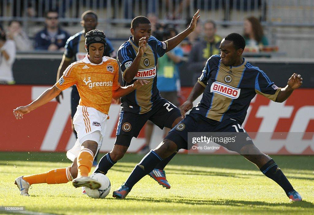 Calen Carr of the Houston Dynamo gets the ball through the defending of Ramon Gaddis and Amobi Okugo of the Philadelphia Union at PPL Park on...
