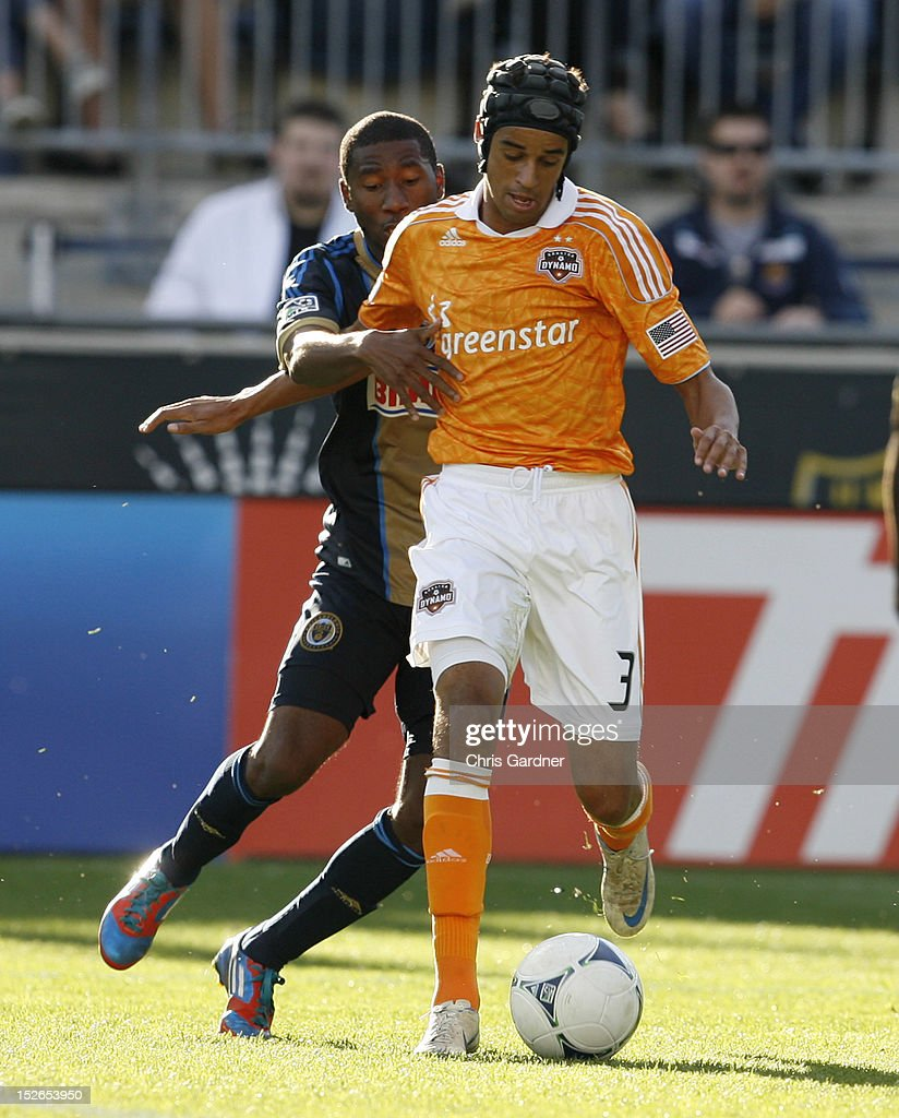 Calen Carr of the Houston Dynamo is held by Ramon Gaddis of the Philadelphia Union at PPL Park on September 23 2012 in Chester Pennsylvania