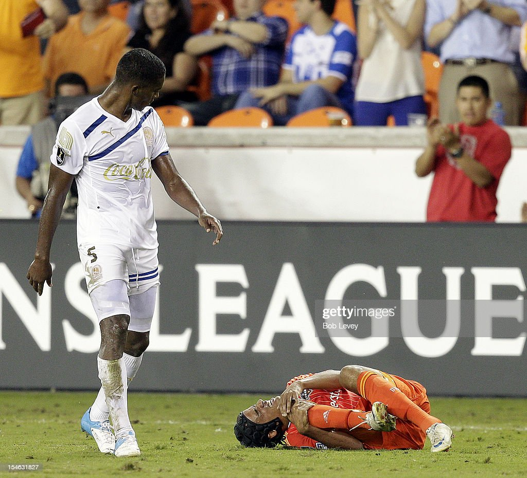Calen Carr of the Houston Dynamo is tripped up by Brayan Beckles of the Olimpia in the second half at BBVA Compass Stadium on October 23 2012 in...