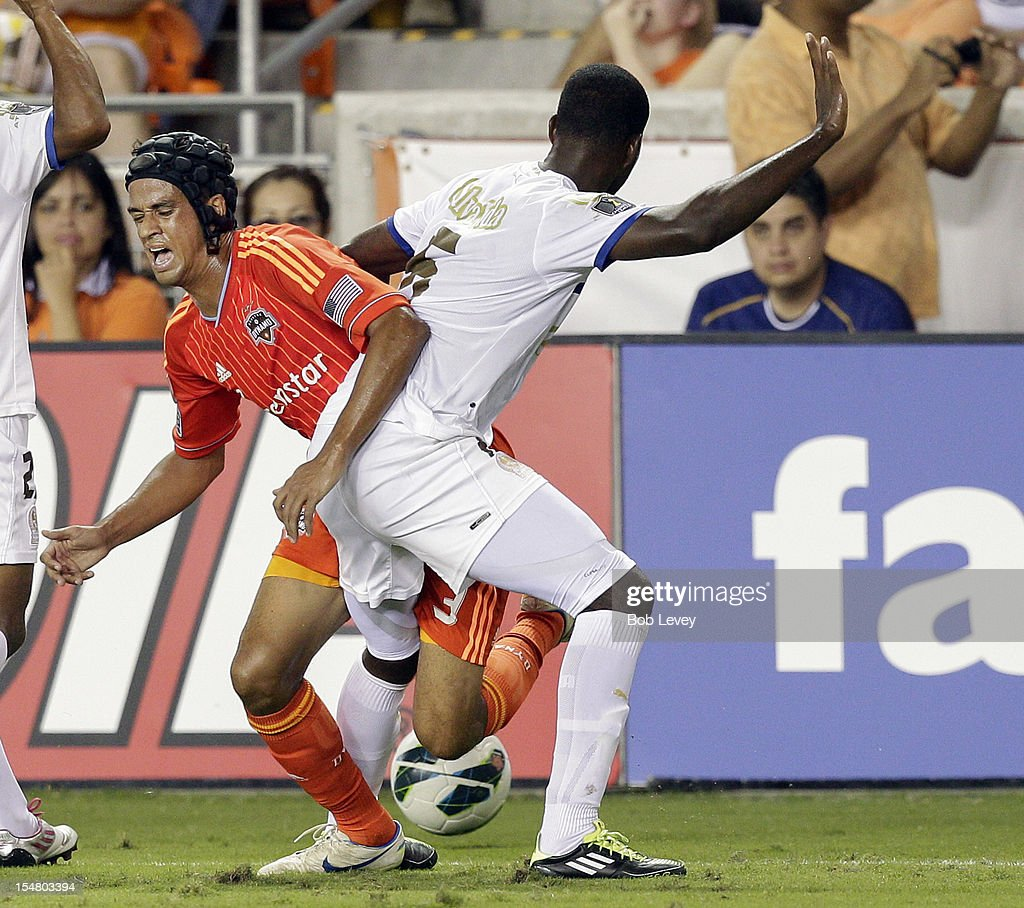 Calen Carr of the Houston Dynamo is tripped up by Brayan Beckles of Olimpia at BBVA Compass Stadium during the CONCACAF League Champions tournament...