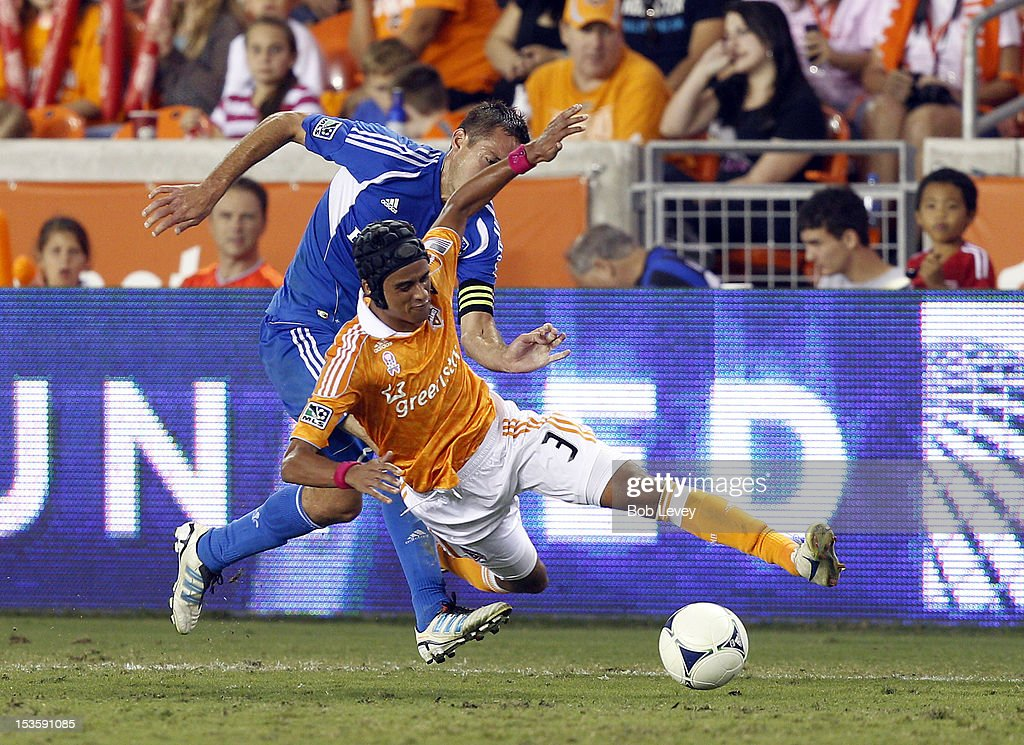 Calen Carr of the Houston Dynamo is tripped up by Davy Arnaud of the Montreal Impact in the second half at BBVA Compass Stadium on October 6 2012 in...