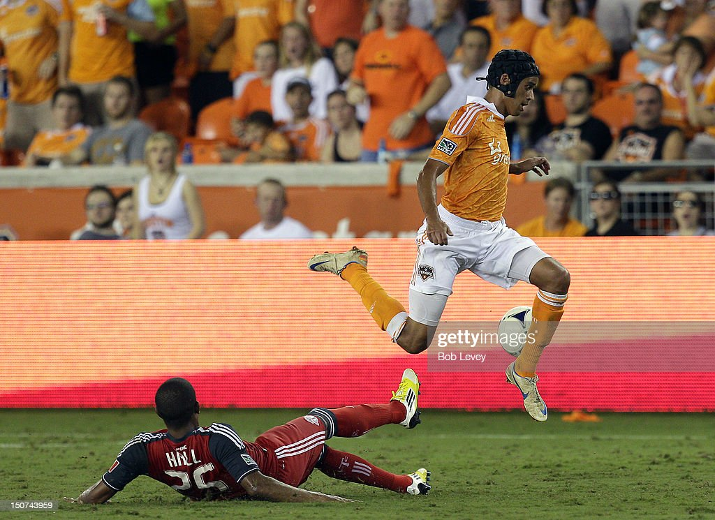 Calen Carr of the Houston Dynamo leaps over a sliding Jeremy Hall of the Toronto FC in the second half at BBVA Compass Stadium on August 25 2012 in...