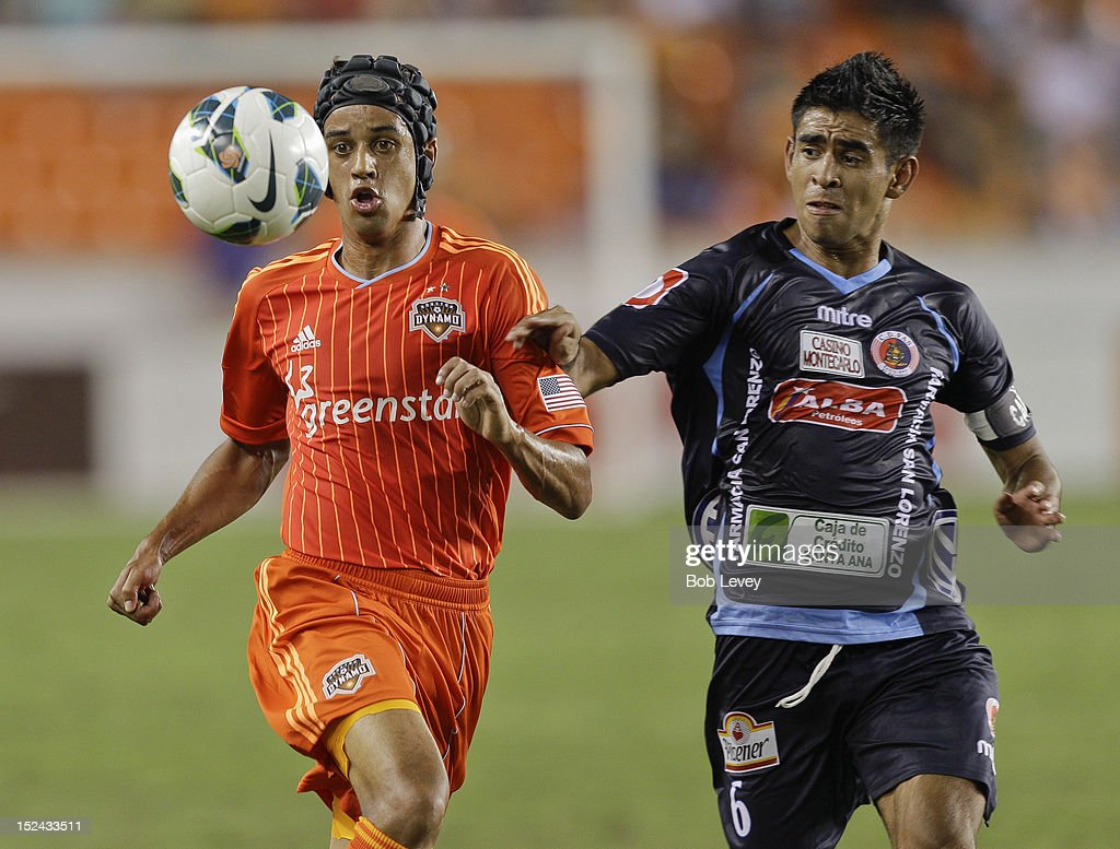 Calen Carr of the Houston Dynamo runs down the ball as Miguel Granadino of the CD FAS defends at BBVA Compass Stadium on September 20 2012 in Houston...
