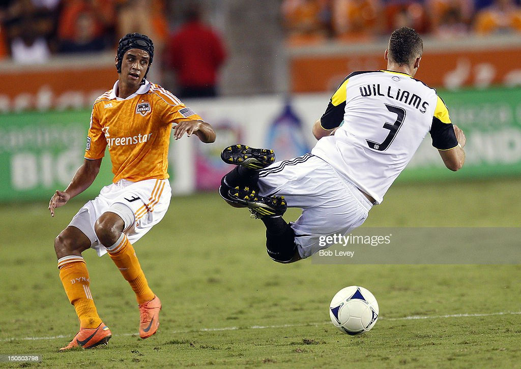 Calen Carr of the Houston Dynamo upends Josh Williams of the Columbus Crew during the second half at BBVA Compass Stadium on August 19 2012 in...