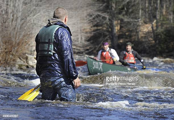 Calen Erskine of Rockport watches another canoe run the rapids after he and his partner Dan Ford capsized their canoe moments before