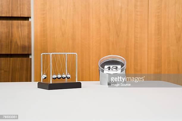A calendar and a newtons cradle on a desk