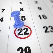 Calendar and blue pushpin. Mark on the calendar at 22.