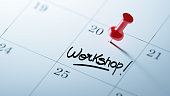 Concept image of a Calendar with a red push pin. Closeup shot of a thumbtack attached. The words Workshop written on a white notebook to remind you an important appointment.