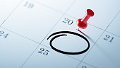 Concept image of a Calendar with a red push pin. Closeup shot of a thumbtack attached. Circle mark written on a white notebook to remind you an important appointment.