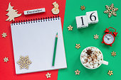 Winter composition. Wooden calendar December 16th Cup of cocoa with marshmallow, empty open notepad with pencil, snowflake, alarm clock on red and green background. Top view Flat lay Mockup