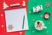 Winter composition. Wooden calendar December 22nd Cup of cocoa with marshmallow, empty open notepad with pencil, snowflake, alarm clock on red and green background. Top view Flat lay Mockup