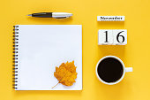 Autumn composition. Wooden calendar November 16 cup of coffee, empty open notepad with pen and yellow oak leaf on yellow background. Top view Flat lay Mockup Concept Hello November