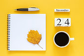 Autumn composition. Wooden calendar November 24 cup of coffee, empty open notepad with pen and yellow oak leaf on yellow background. Top view Flat lay Mockup Concept Hello November