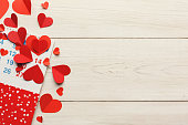 Calendar page with the red hearts on Saint Valentines date. Reminder on white wooden table top view, copy space