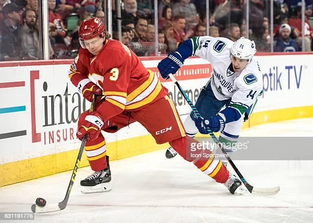 Calgary Flames Defenceman Jyrki Jokipakka defends the puck from Vancouver Canucks Right Wing Alexandre Burrows during a game between the Calgary...