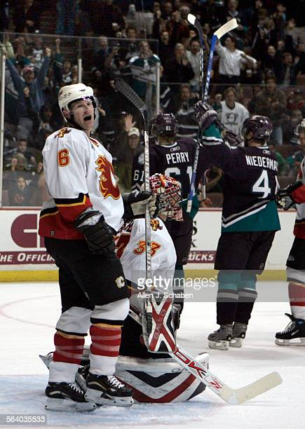 Calgary Flames defender Jordan Leopold left lets out a yell with goalie Brian Boucher as Mighty Ducks of Anaheim players Rob Niedermayer and Corey...
