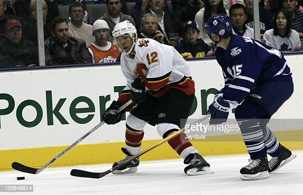 Calgary Flames forward Jarome Iginla looks to elude the checking of Toronto Maple Leaf defenceman Tomas Kaberle in action at the Air Canada Centre in...