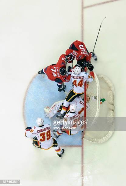 Calgary Flames goalie Brian Elliott and defenseman Matt Bartkowski make a second period save on a shot by Washington Capitals left wing Andre...