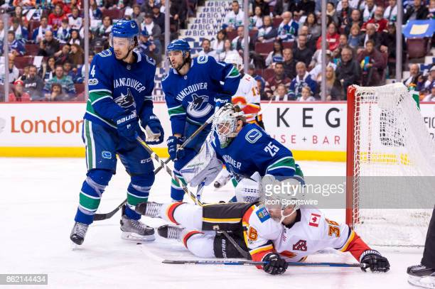 Calgary Flames Winger Freddie Hamilton tracks the play as Calgary Flames Right Wing Troy Brouwer is checked to the ice by Vancouver Canucks...