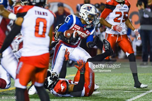 Calgary Stampeders players having a hard time stopping Montreal Alouettes running back Tyrell Sutton with the ball during the Calgary Stampeders...