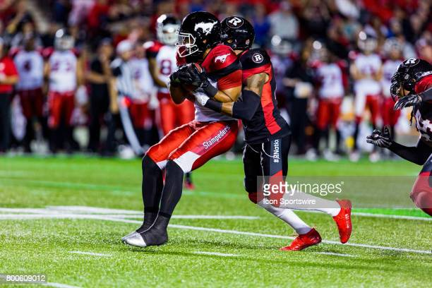 Calgary Stampeders wide receiver Lemar Durant attempts to break a tackle by Ottawa RedBlacks defensive back AJ Jefferson during Canadian Football...