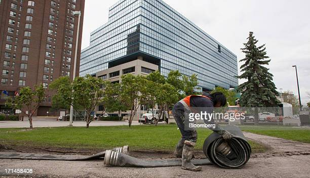 Calgary Transit employee Geoffrey Gonzaga lays out a hose to pump out water from the city's light rail transit tunnels after flooding in Calgary...