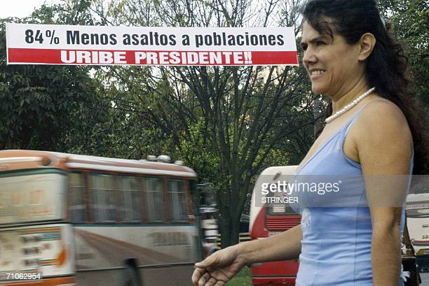 A women passes in front the posters in favour of Colombian president and candidate Alvaro Uribe May 26 in Cali Colombians look set to reelect Uribe...